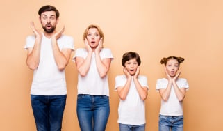 picture of a family of four all dressed in white t-shirts and jeans with shocked looks on their face
