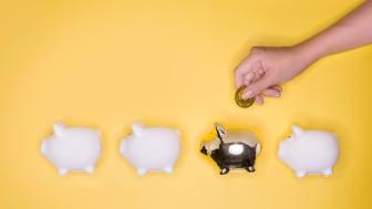 A hand putting money into a gold piggy bank
