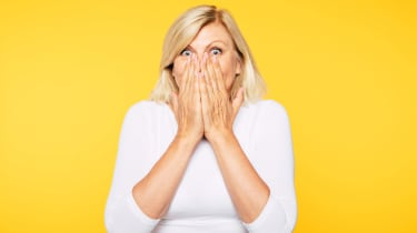 Woman with surprised look on face covering her mouth