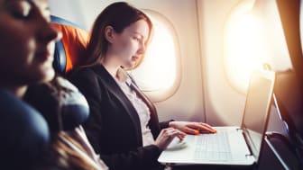 Female entrepreneur working on laptop sitting near window in an airplane.