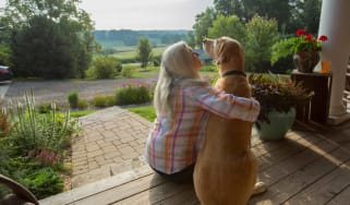A woman sits on her front porch with her dog.