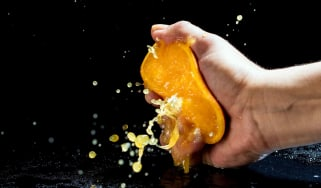 A person aggressively squeezing an orange