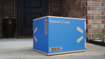 A Walmart-delivered box sits on the porch of a house