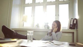 picture of a woman working in her home office with her feet up on her desk while talking on the phone