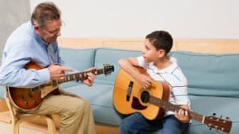 Teacher instructing boy on how to play guitar