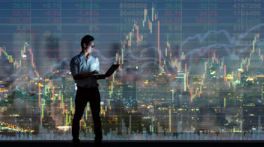 Asian businessman standing and using the smart mobile phone showing the Stock market chart over the cityscape background at night time, Businesstechnology and trading concept