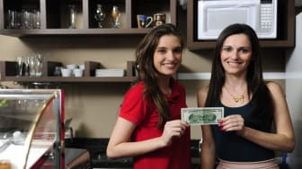 successful small business: happy owner of a cafe and employee showing money they have earned