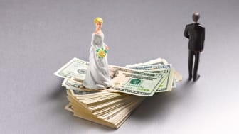 picture of bride doll on stack of money with groom doll turning his back on bride