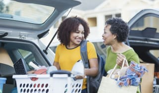 A mature African-American woman helping her daughter relocate, perhaps into an apartment or college dorm.They are in a parking lot unloading their cars. The young woman is carrying a laundry