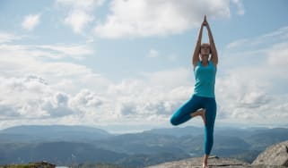 Young woman practicing yoga high up on top of mountain Ulriken, in Bergen, Norway, overlooking mountain range - tree pose or Virksasana.