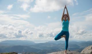 Young woman practicing yoga high up on top of mountain Ulriken, in Bergen, Norway, overlooking mountain range - tree pose or Virksasana.