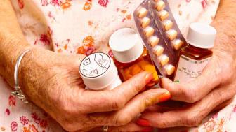 Senior female holding pill bottles