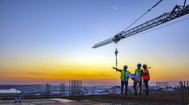 Three people working on construction site
