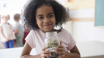 Photo of a child holding a jar with money for college