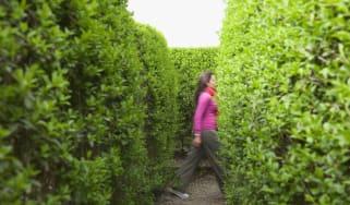 Hispanic woman walking in hedge maze