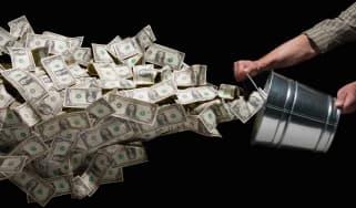 A man dumps a bucket full of cash.