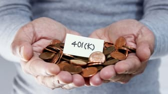 """picture of person holding pennies and a note that says """"401(k)"""""""