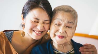 A mom and grown daughter smile and hug.