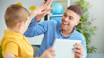 Boy high-fiving daycare worker