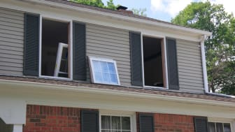A home with windows removed and replacement windows ready to be installed - an effective way to cut energy costs.
