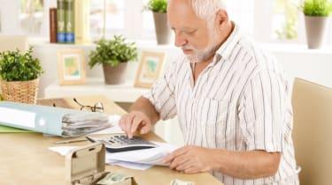 Senior man doing calculation at home