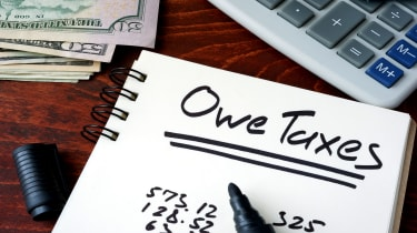"picture of notebook with ""owe taxes"" written on it and next to money and a calculator"