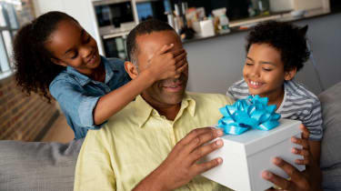 Photo of father opening gift box as two young children watch