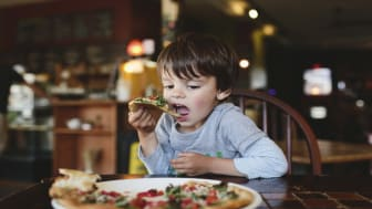 A boy, child eating pizza in a restaurant.