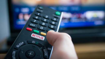 Southampton, England - July 31, 2017: Using a television remote control with dedicated Netflix button, TV in the background.