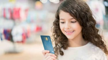 Girl holding parent's credit card in store