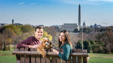 Young couple Daniel Bortz and his wife, Alexandra, sitting on a park bench overlooking Washington, D.C.