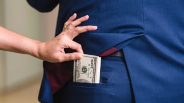 A hand snatches cash out of the back pocket of a man's suit pants.