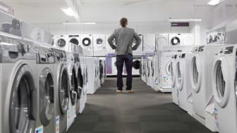 Man looking at washer/dryer displayer at appliance store.