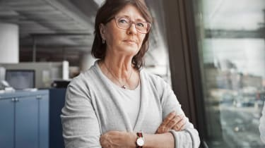 An older woman stands in an office with arms crossed.