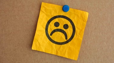 picture of a sad face drawn on a post-it note pinned to a bulletin board