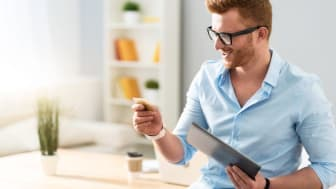 Unlimited source of money. Cheerful handsome man holding tablet and credit card while leaning on the table