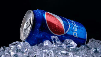A blue Pepsi can sits atop ice