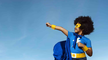 A young girl dressed as a superhero strikes a powerful pose