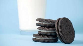 Three Oreo cookies stacked atop one another, with a fourth resting against the stack