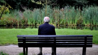 A retiree sits on a park bench all by himself.
