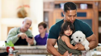 Father holding child and dog with grandfather and another child in the background
