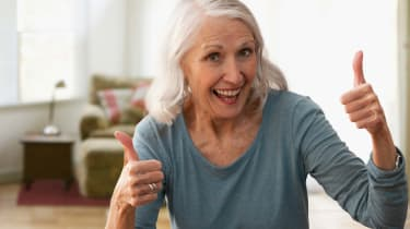 A smiling gray-haired woman gives two thumbs up.