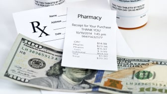 Pharmacy receipt with prescription bottle and prescription on neutral background.Label/document is totally fictitious and any resemblance to any actual product is purely coincidental.