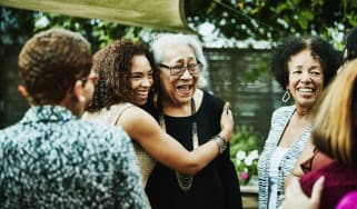 Mature daughter embracing mother after outdoor family dinner party
