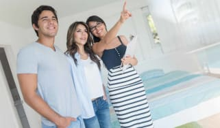 Young couple smile as they talk with a real estate agent.