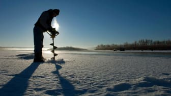 Fisherman drilling a hole in the ice of a frozen North Dakota lake