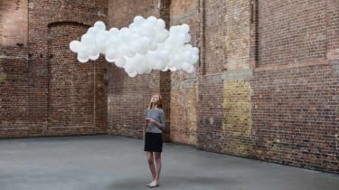 A cloud of white balloons hovers over a woman.