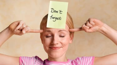 "A woman with a Post-It Note on her forehead that reads, ""Don't Forget."""