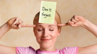 """A woman with a Post-It Note on her forehead that reads, """"Don't Forget."""""""