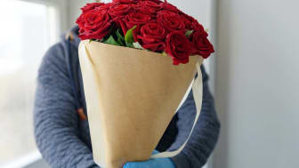 contactless flower delivery, male courier in a protective face mask, medical gloves with a bouquet of red roses, the concept of the decline of the flower business (contactless flower delivery